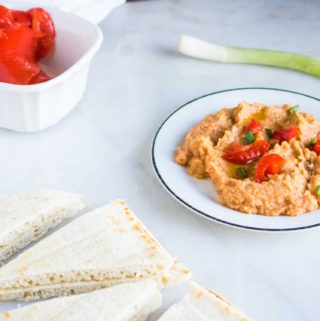 red pepper hummus on white plate