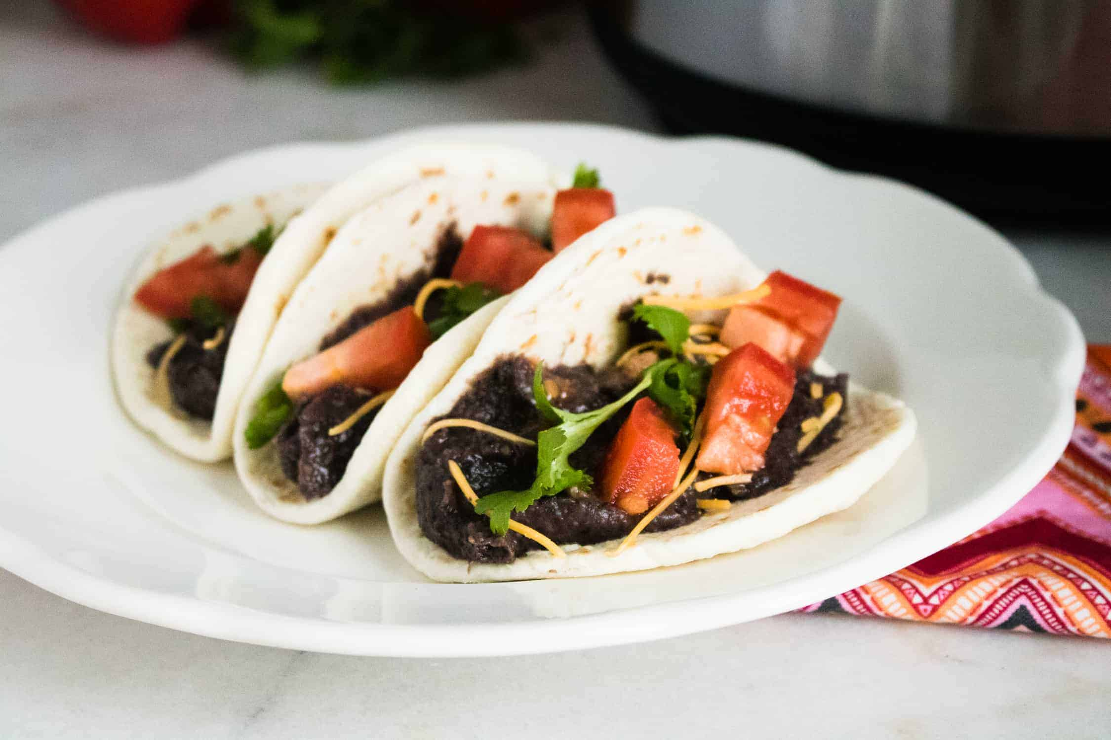black bean soft tacos on white plate