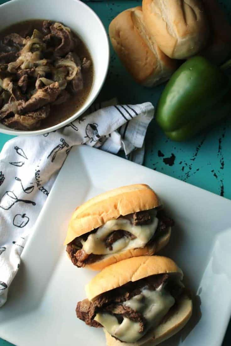 philly cheesesteak meat on hoagie buns on white plate