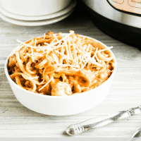 pasta with cheese on top in white bowl