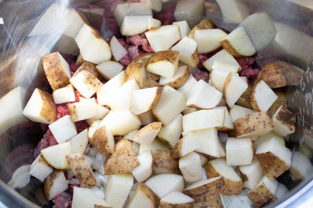 dice potatoes in pan with beef and onions for instant pot goulash