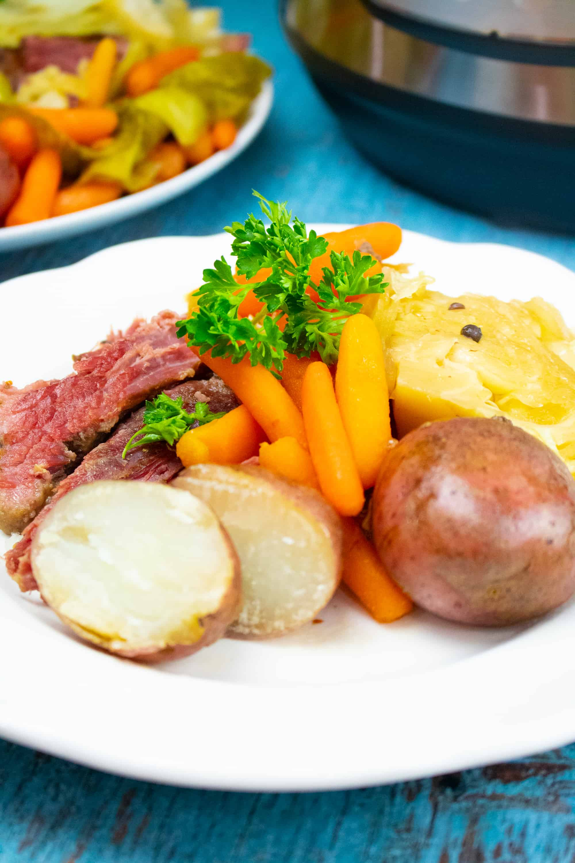 instant pot corned beef, potatoes, carrots and cabbage on white plate