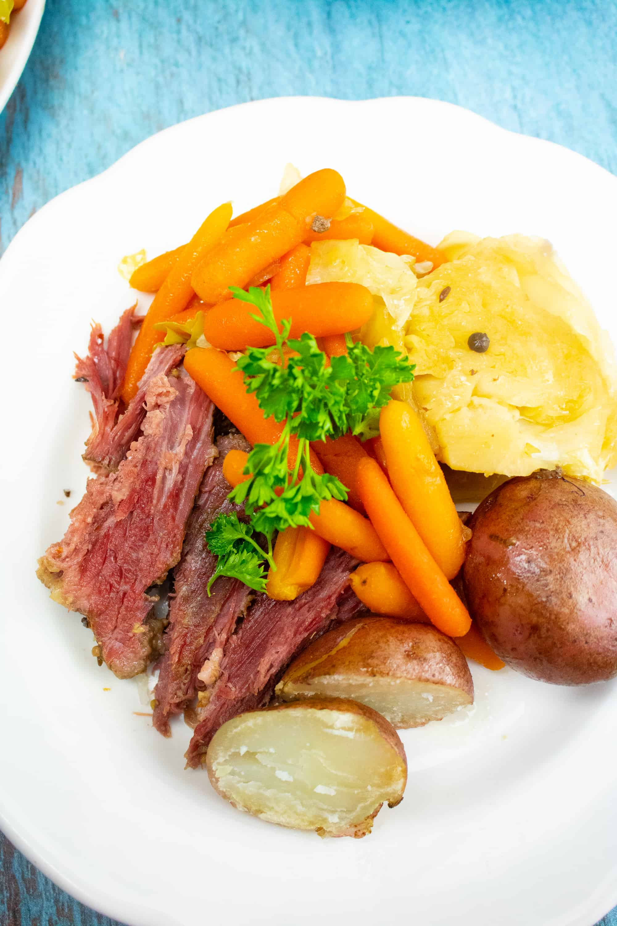 corned beef with potatoes, carrots and cabbage on a white plate