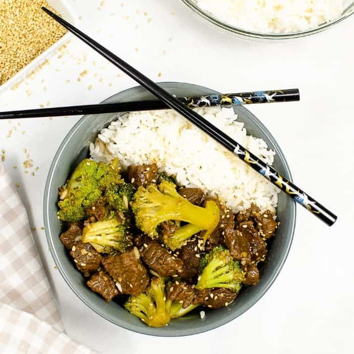 beef and broccoli in grey bowl with chopsticks