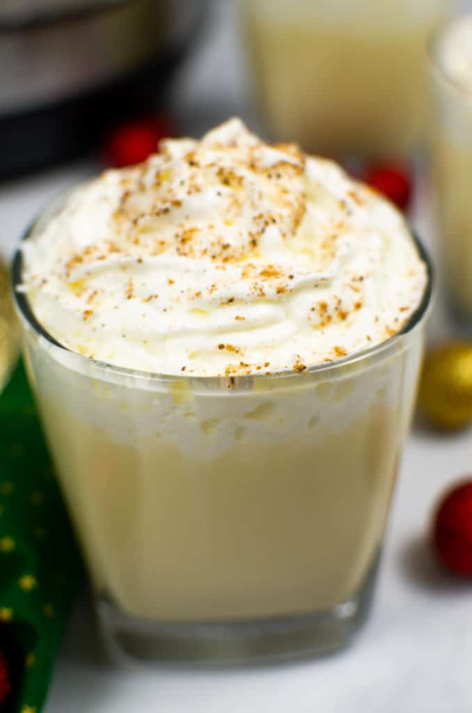 Instant Pot Eggnog in clear glass topped with whipped cream and nutmeg