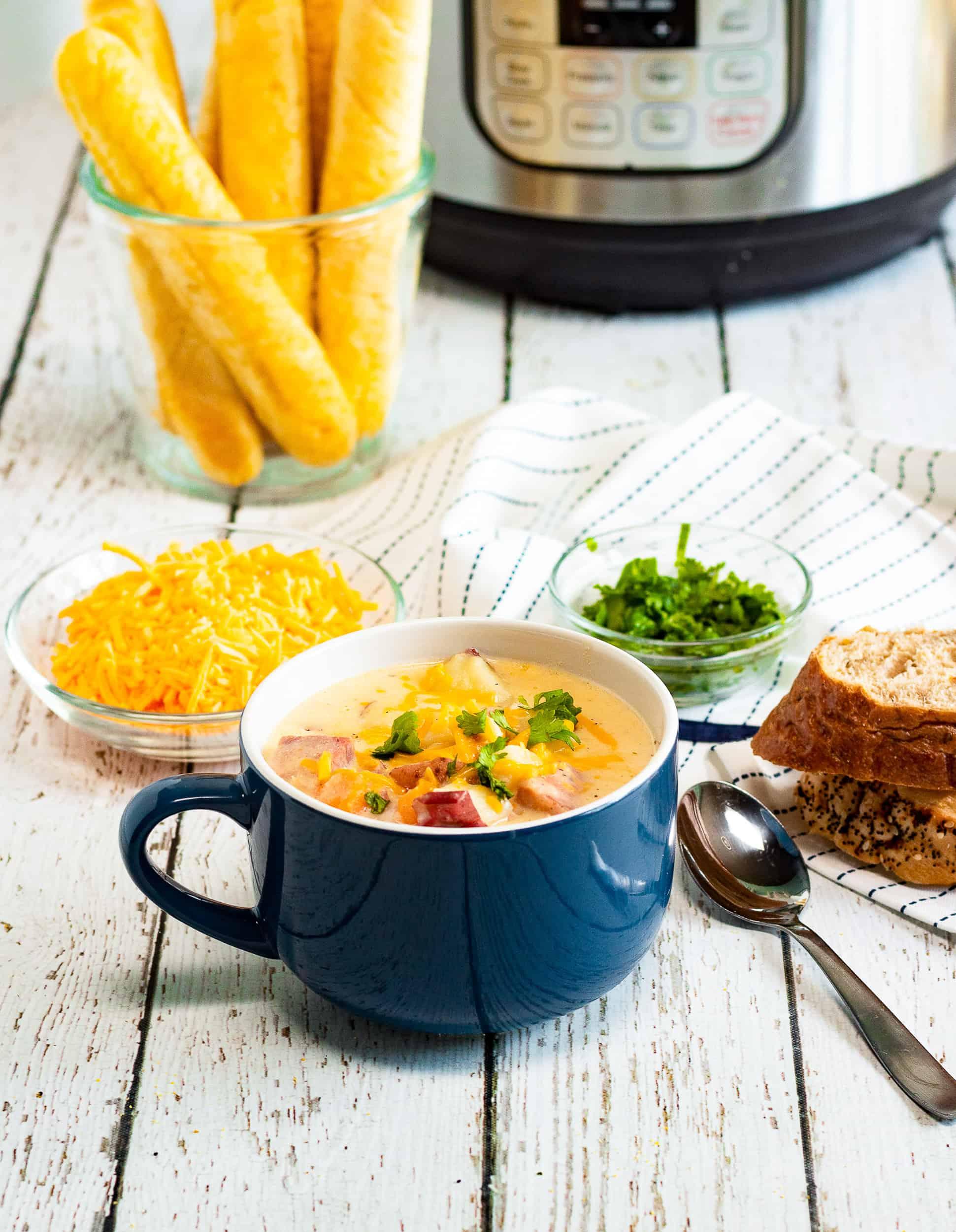 Ham potato soup in a blue soup bowl with a handle