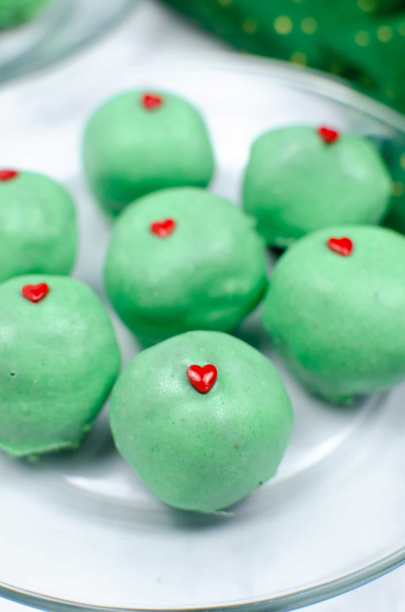 plate of cake pops christmas truffles with green chocolate covering and a red heart on white plate