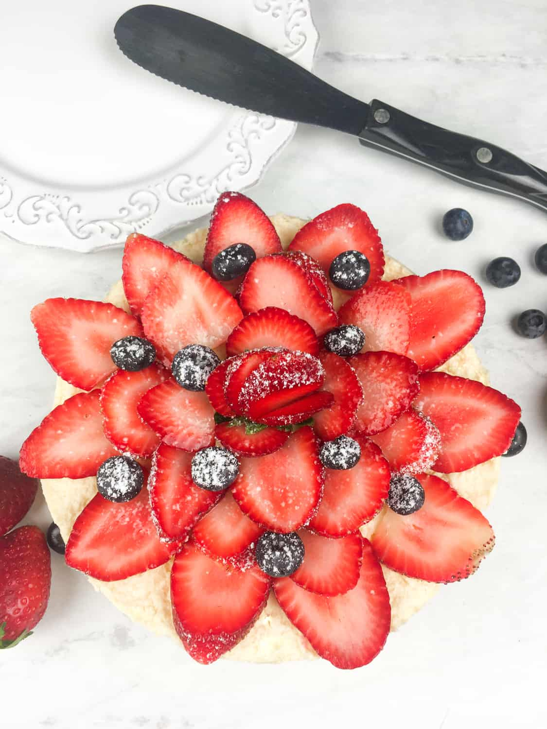 strawberries and blueberries decorating a cake, arranged in a flower shape