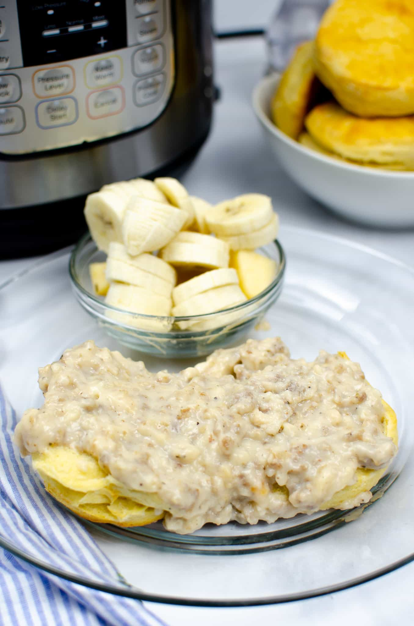 instant pot sausage gravy on clear plate with glass bowl of sliced bananas and white bowl full of biscuits in the background
