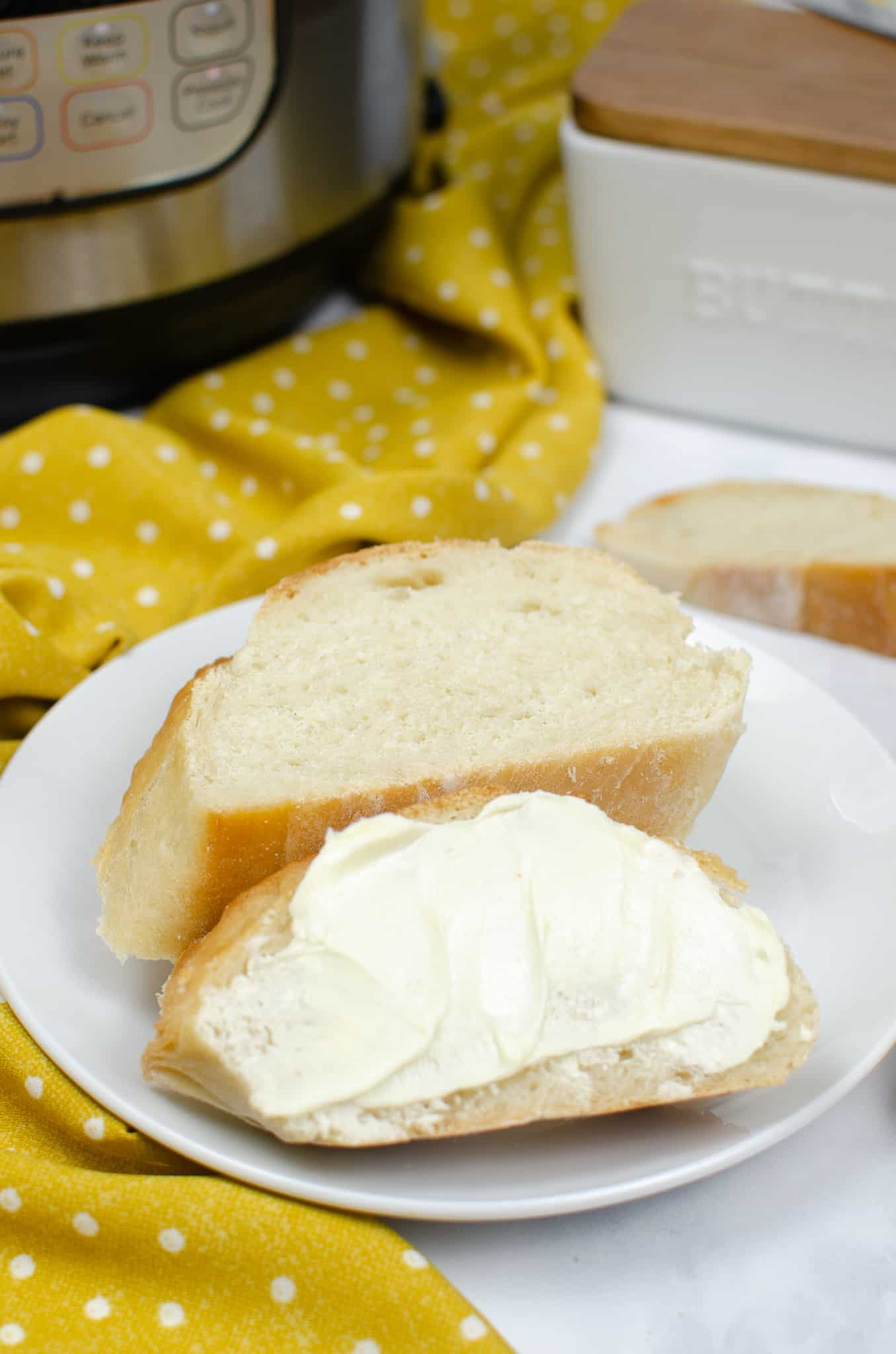 french bread instant pot bread recipe two slices of bread on white plate. One is slathered with butter.