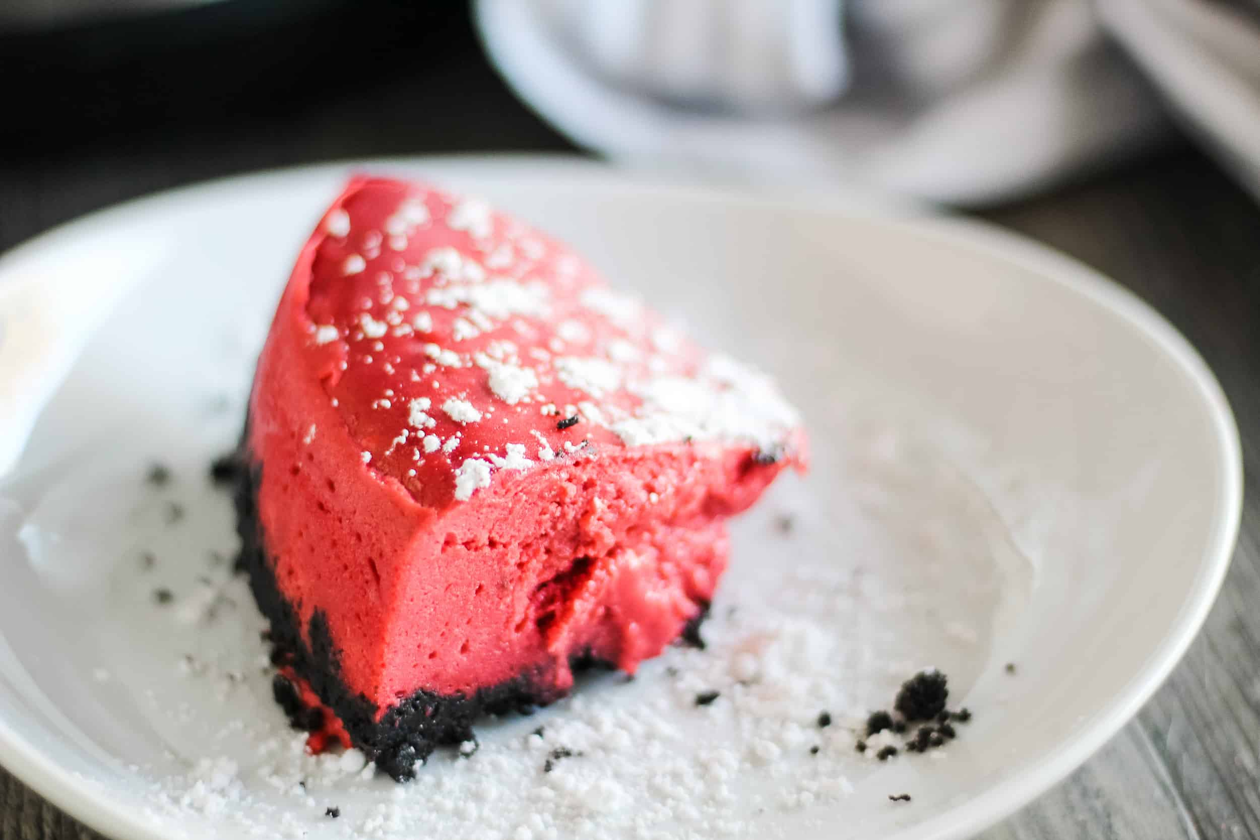 red velvet cheesecake with powdered sugar on white plate
