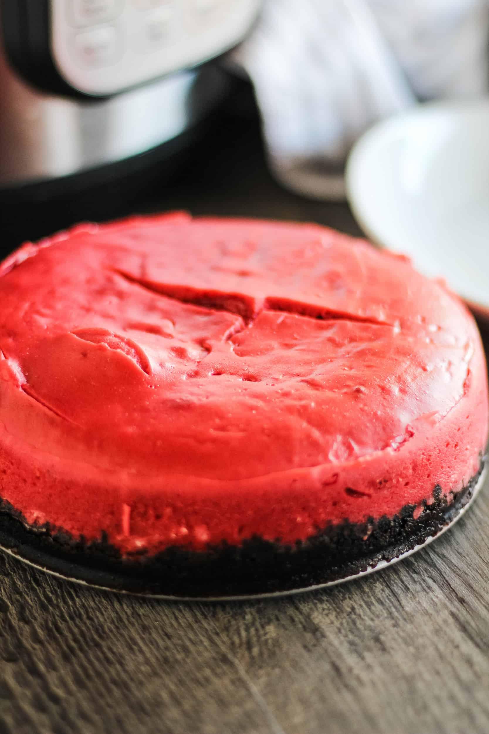 red velvet cheesecake cooling on dark wood table