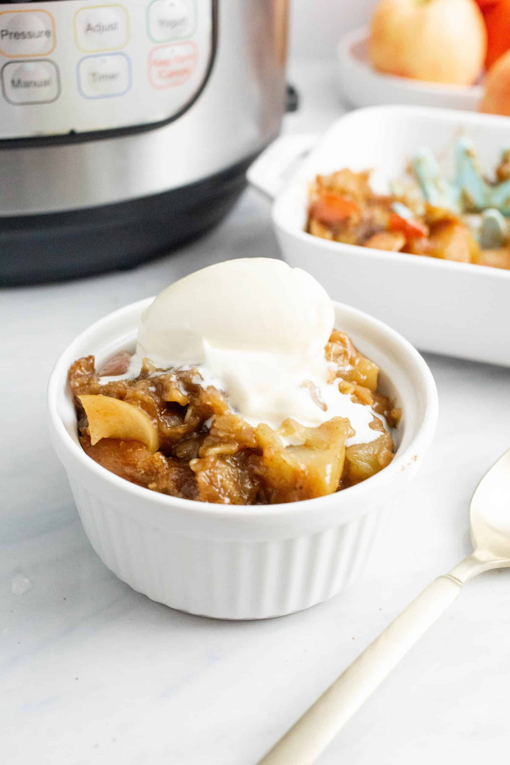 instant pot apple crisp in white bowl with a scoop of vanilla ice cream on top and instant pot in the background