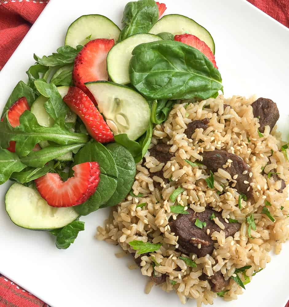 Instant Pot Beef and Rice on white plate with salad