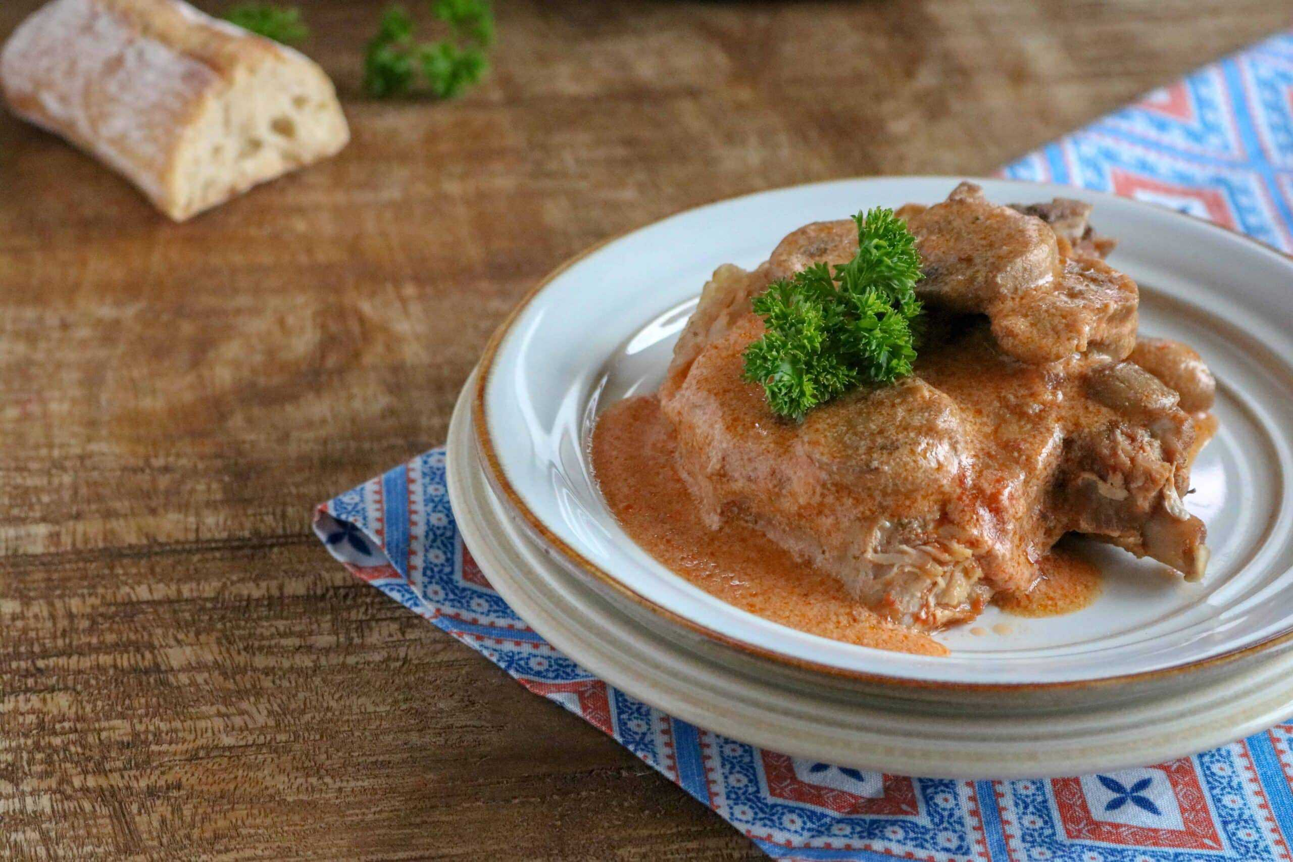 pork chops in creamy pink sauce on white plate