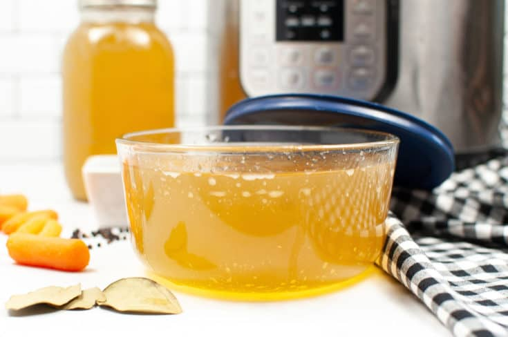 bone broth in clear glass bowl with instant pot behind it