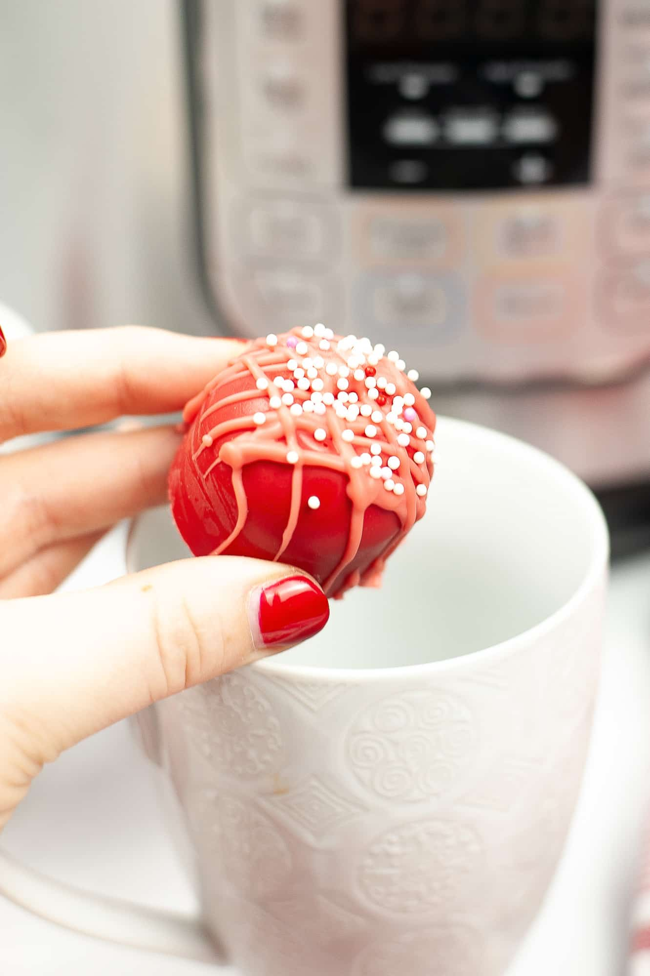 hand with red painted finger nails holding a red hot cocoa bomb over a white mug