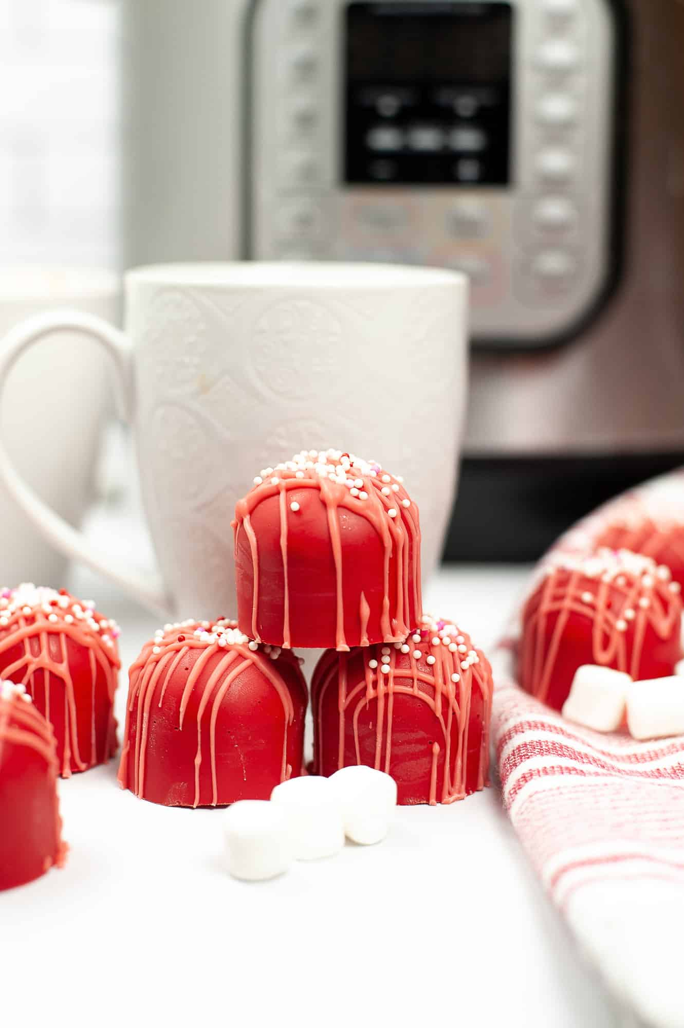 red hot cocoa bombs stacked in front of white mug