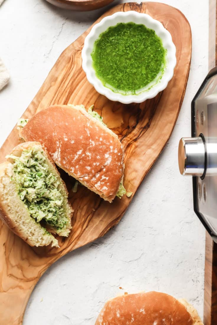 chicken chimichurri sandwich on cutting board with bowl of chimichurri sauce next to it