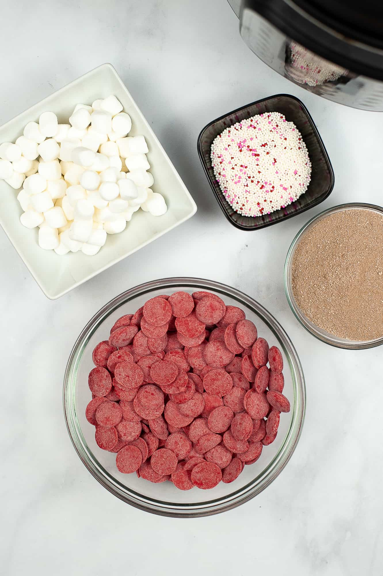 ingredients for hot chocolate bombs in ingredient bowls on counter top