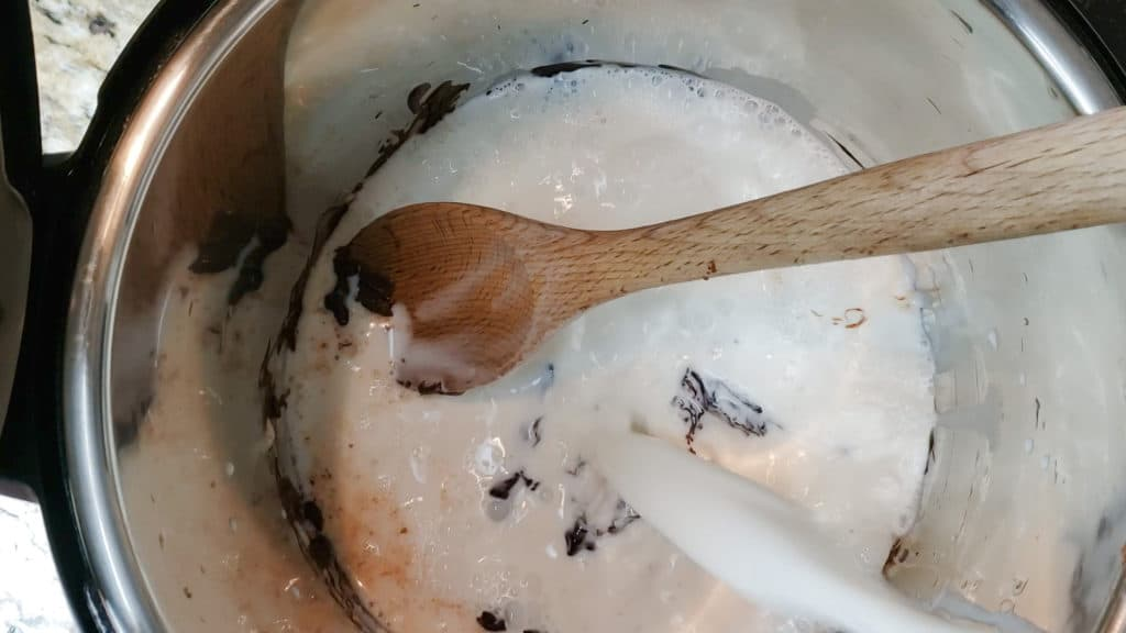 mixing Instant Pot Hot Chocolate in inner pot with wooden spoon