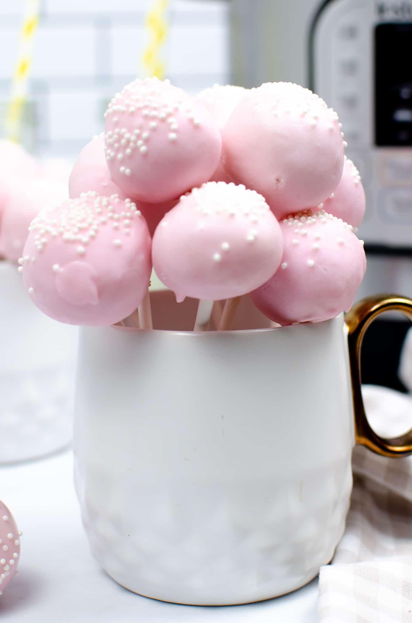 pink cake pobs in white mug