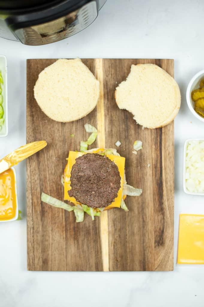 big mac in process photo showing cheeseburger with 2nd hamburger patty on it