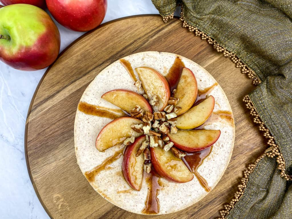 cheesecake with apples and caramel on wood board