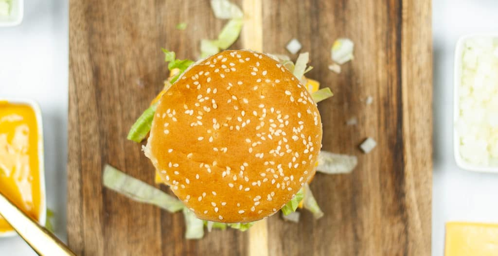 big mac in process photo showing cheeseburger overhead shot with bun on top with sesame seeds on it