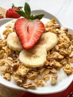 yogurt with granola, bananas and strawberries in white bowl