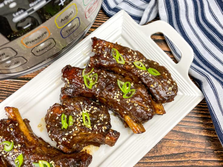 sticky ribs on white platter with chopped green onions on top