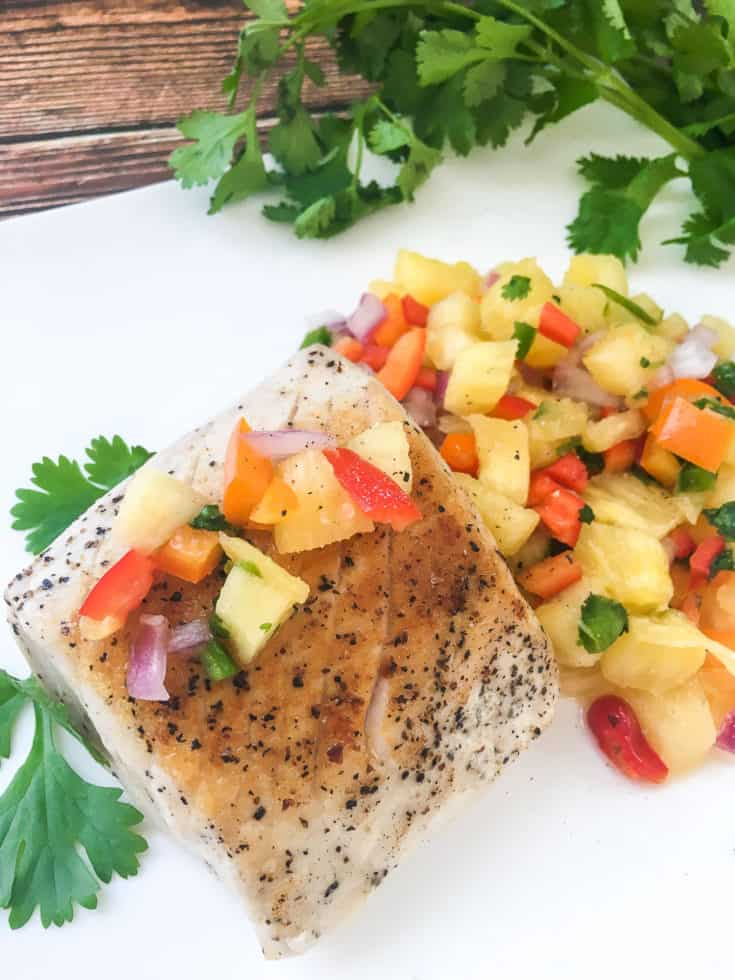 swordfish with fruit salsa on white plate