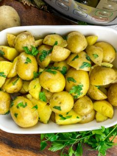 roasted gold potatoes in white serving dish