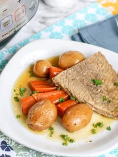 beef roast on white plate with potatoes and carrots
