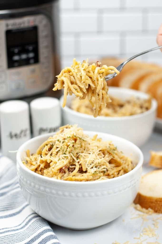 Instant Pot carbonara in white bowl with a fork full of pasta lifted above the bowl