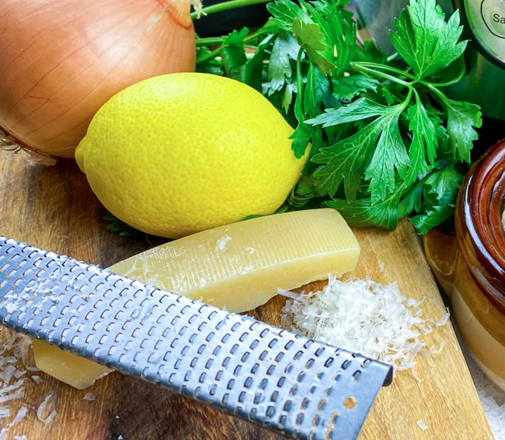 parmesan cheese with grater on cutting board