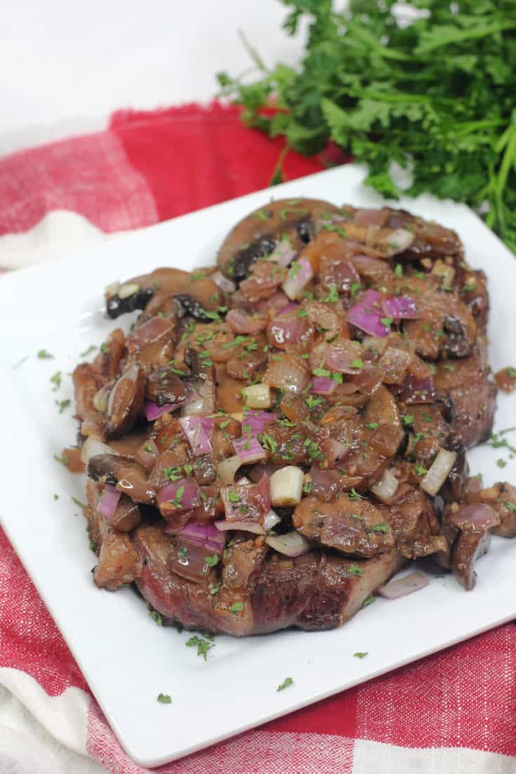 instant pot steak with mushrooms and onions on white plate