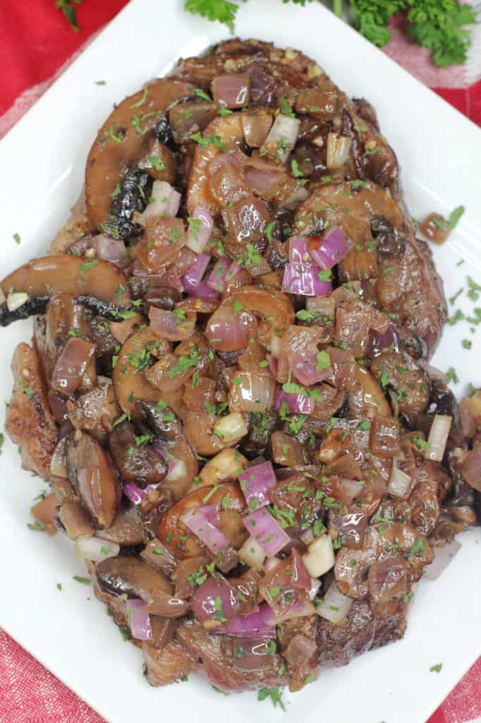 tasty steak with mushroom and onions on top
