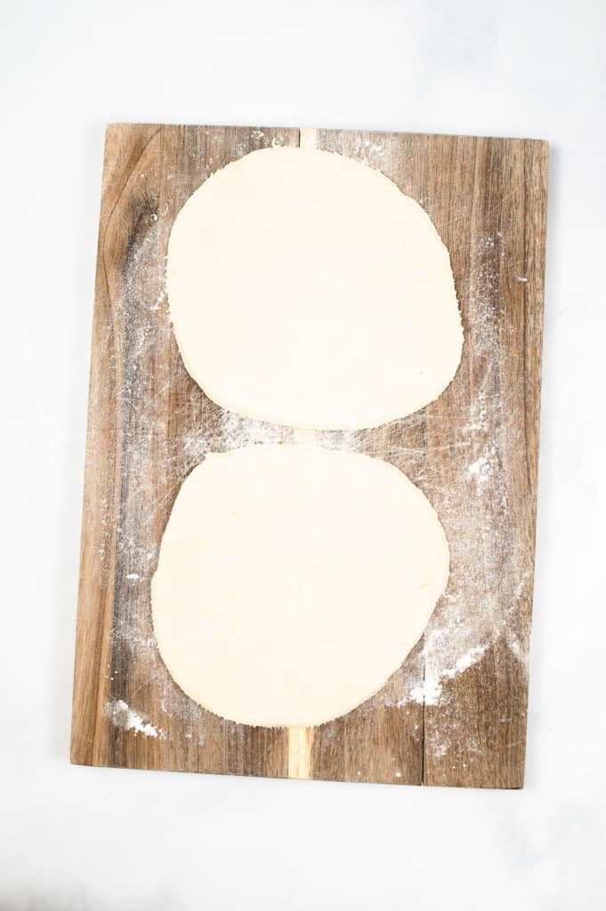 pizza dough on wooden cutting board