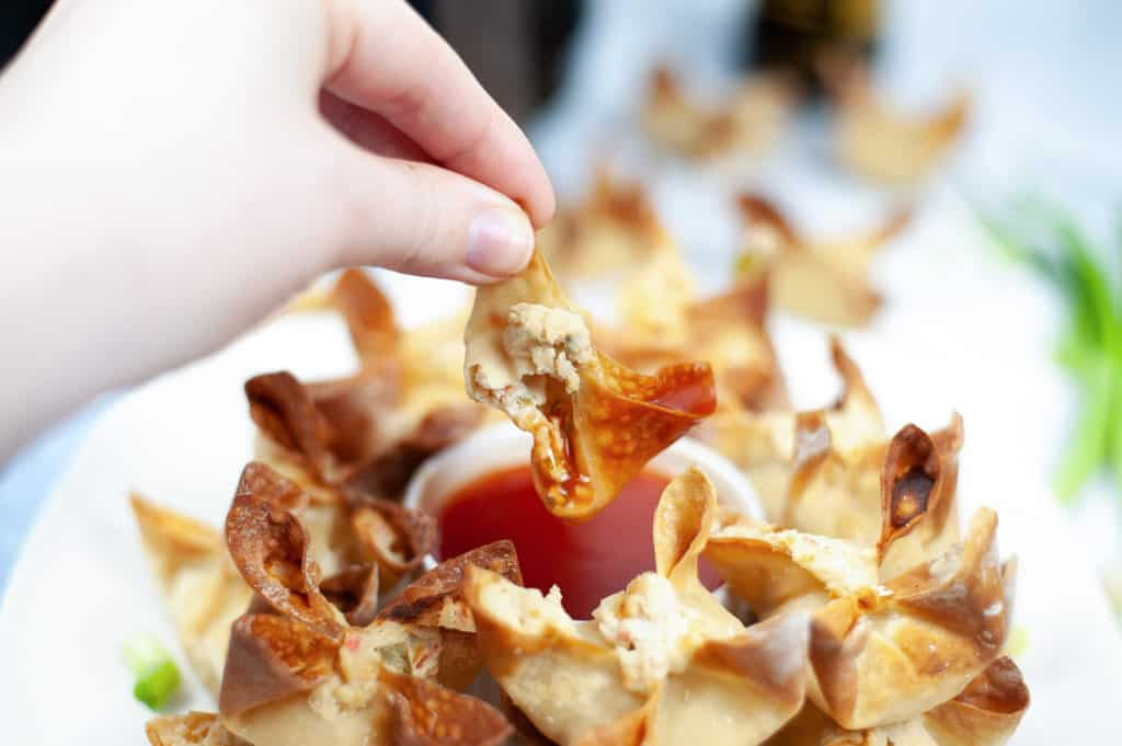 holding crab rangoon dipped in sauce