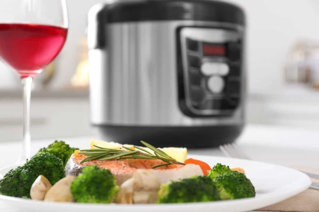 Plate with salmon steak and garnish prepared in multi cooker on table